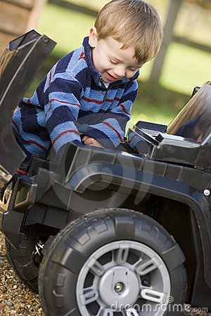 Young boy playing outdoors with toy truck smiling