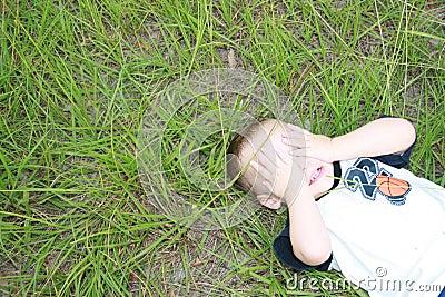 Young boy playing Peek a Boo
