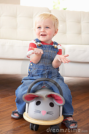 Young Boy Playing With Ride On Toy Mouse At Home