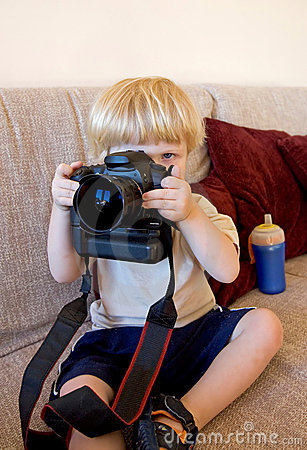 Young boy playing with SLR digital camera