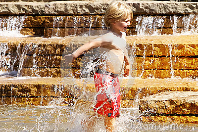 Young boy playing in water fountain