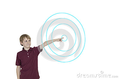 Young boy pointing to digitally designed concentric circles over white background