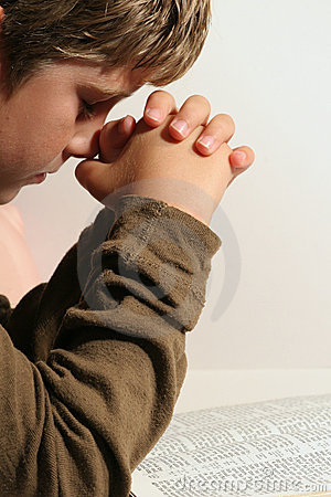 Young boy praying - vertical
