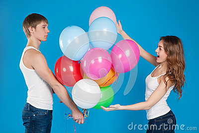 Young boy presenting baloons to a girl.