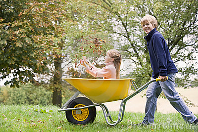 Young boy pushing girl in wheelbarrow