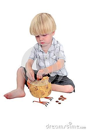 Young boy putting money into a piggy bank