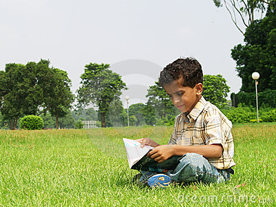 Young boy reading in field