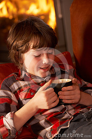 Young Boy Relaxing With Hot Drink By Cosy Log Fire