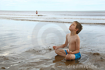 Young boy relaxing in lotus yoga pose on beach