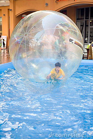 Young boy in rubber ball floating on water
