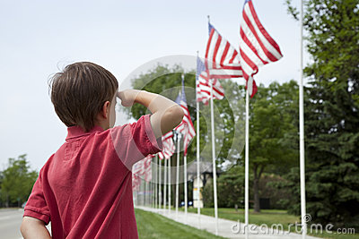 Young boy saluting American flags on Memorial Day
