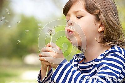 Young Boy Sitting In Field Blowing Dandelion
