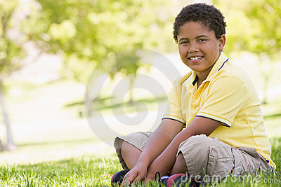 Young boy sitting outdoors