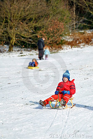 Young boy in sledge sliding snowy hill, winter fun