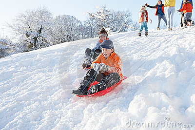Young Boy Sledging Down Hill With Family Watching