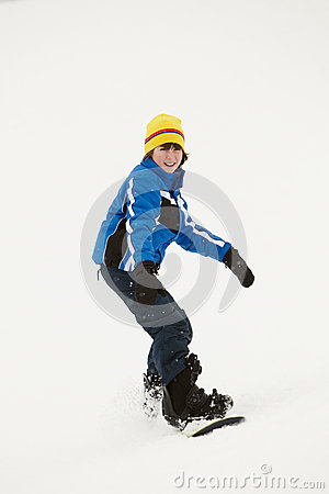 Young Boy Snowboarding Down Slope On Holiday