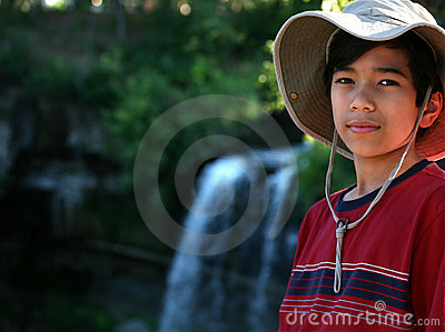 Young boy standing nect to water fall