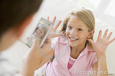 Young boy taking picture of smiling young girl
