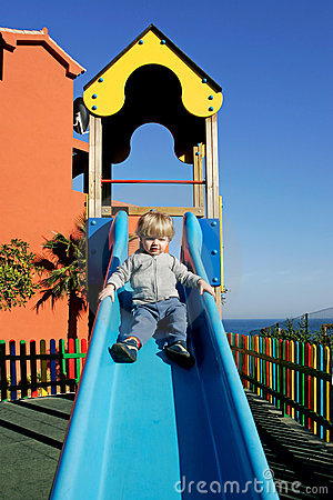 Young boy or toddler coming down a slide in the sun