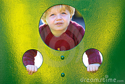 Young boy or toddler looking through holes in a wall in a playground