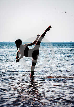 Young boy training karate in sea