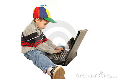 Young boy types on laptop
