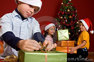 Young boy unwrapping Christmas gift