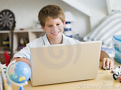 Young Boy Using A Laptop In His Bedroom