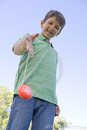 Young boy using yo yo outdoors smiling