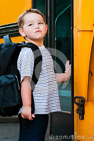 Young boy waits to board bus for school