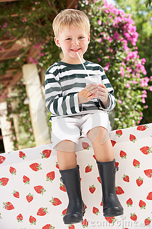 Young Boy Wearing Boots Drinking Milkshake
