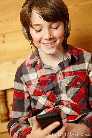 Young Boy On Wooden Seat Listening To MP3 Player
