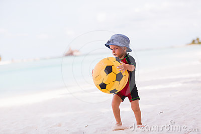 Young boy with yellow ball on the beach