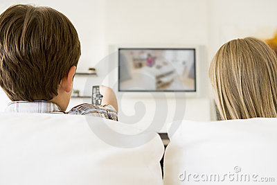 Young boy and young girl in living room with remot