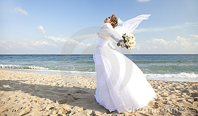 Young bride on the beach wqith flowers