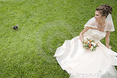 Young bride on a grass with pigeon