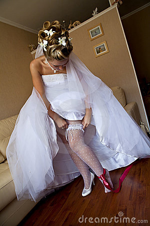 Young bride setting the garter