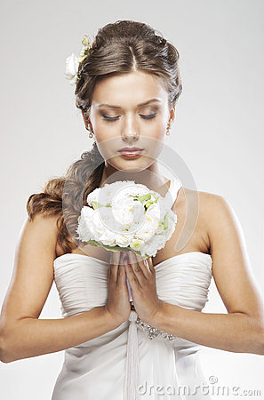 A young bride in a white dress holding flowers