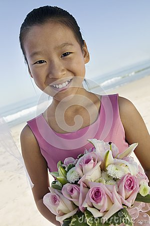 Young Bridesmaid with flowers on beach (portrait)