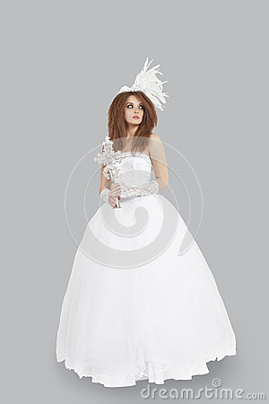 Young bridge in wedding dress holding crucifix while looking away over light gray background