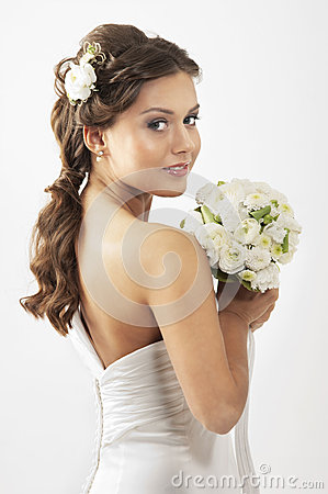 A young brunette bride holding a bouquet of roses