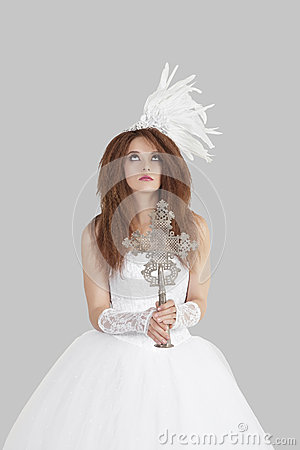 Young brunette bride in wedding gown holding crucifix while looking up over light gray background