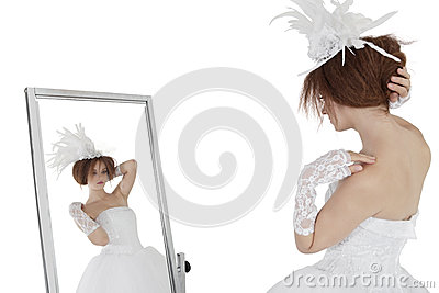 Young brunette bride in wedding gown looking at herself in mirror over white background