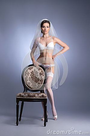 A young brunette bride in white erotic lingerie
