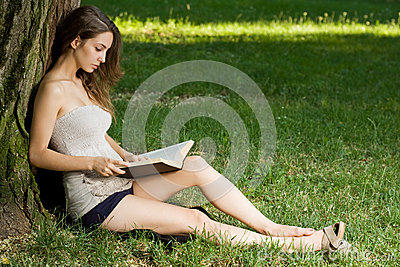 Young brunette enjoying book outdoors.