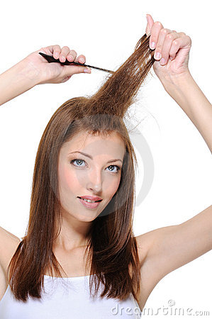 Young brunette girl doing backcombing with comb