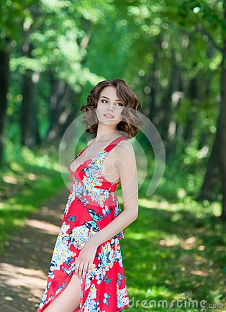 Free Young Brunette Girl In Red Dress Posing On Alley In Summer Park Against Trees Stock Photo - 106884370