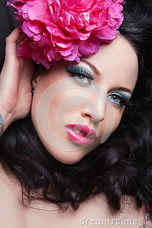 Young brunette girl with pink flower in her hair.