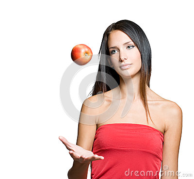 Young brunette juggling fresh apple.