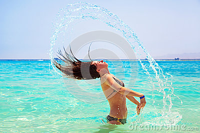 Young brunette jumping out of turquoise water of Red Sea